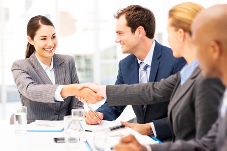 Happy young businesswomen shaking hands while sitting with multi-ethnic colleagues in meeting. Horizontal shot.